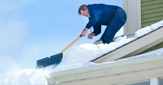 man-shoveling-snow-off-of-house-roof_573x300