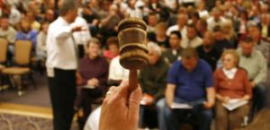Sam Marshall of Hudson & Marshall (not seen) prepares to drop his gavel signaling bidding is over and another house is sold at an auction of foreclosed homes in Denver April 19, 2008. Over 400 people attended the auction selling almost 100 lender-owned properties. REUTERS/Rick Wilking (UNITED STATES) - RTR1ZOCL